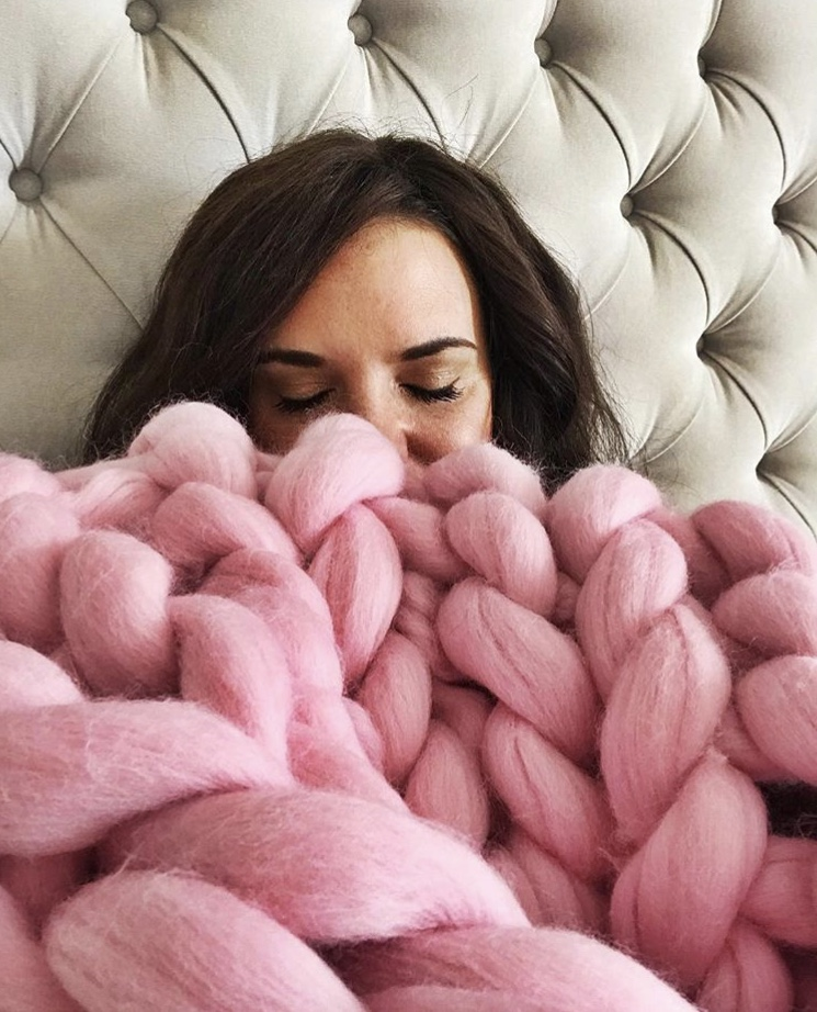 Girl in bed with pink chunky knit throw