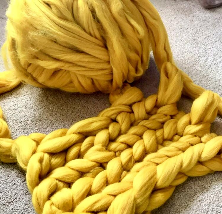 chunky merino wool ball in yellow knitting
