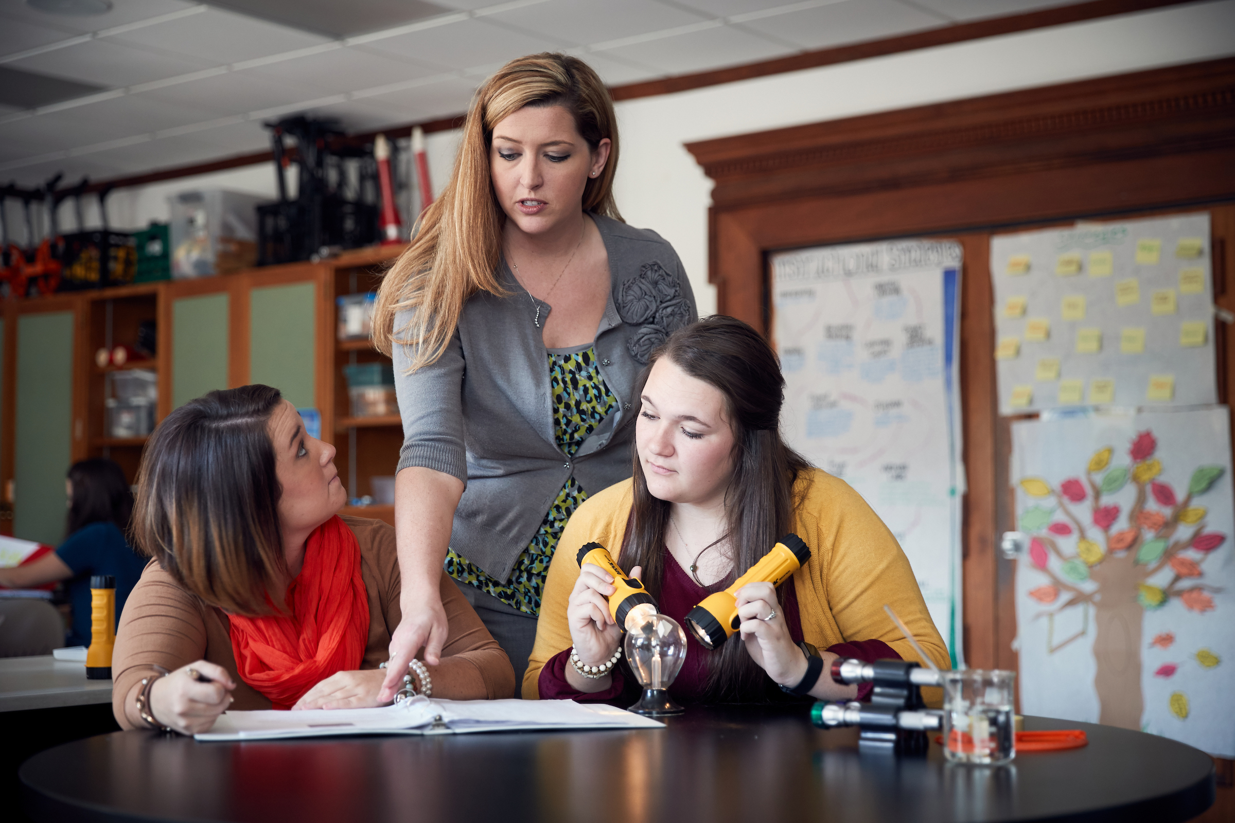 A teacher helps her students with a science project.