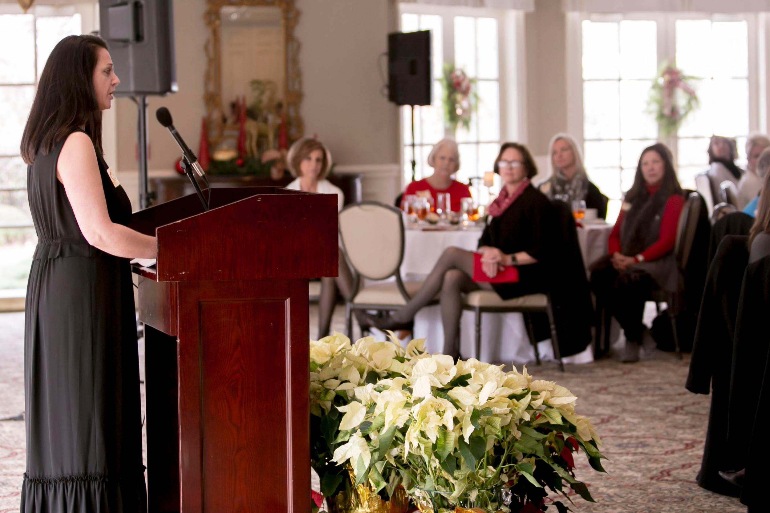 A Women's Educational Scholarship recipient gives a speech at an event.