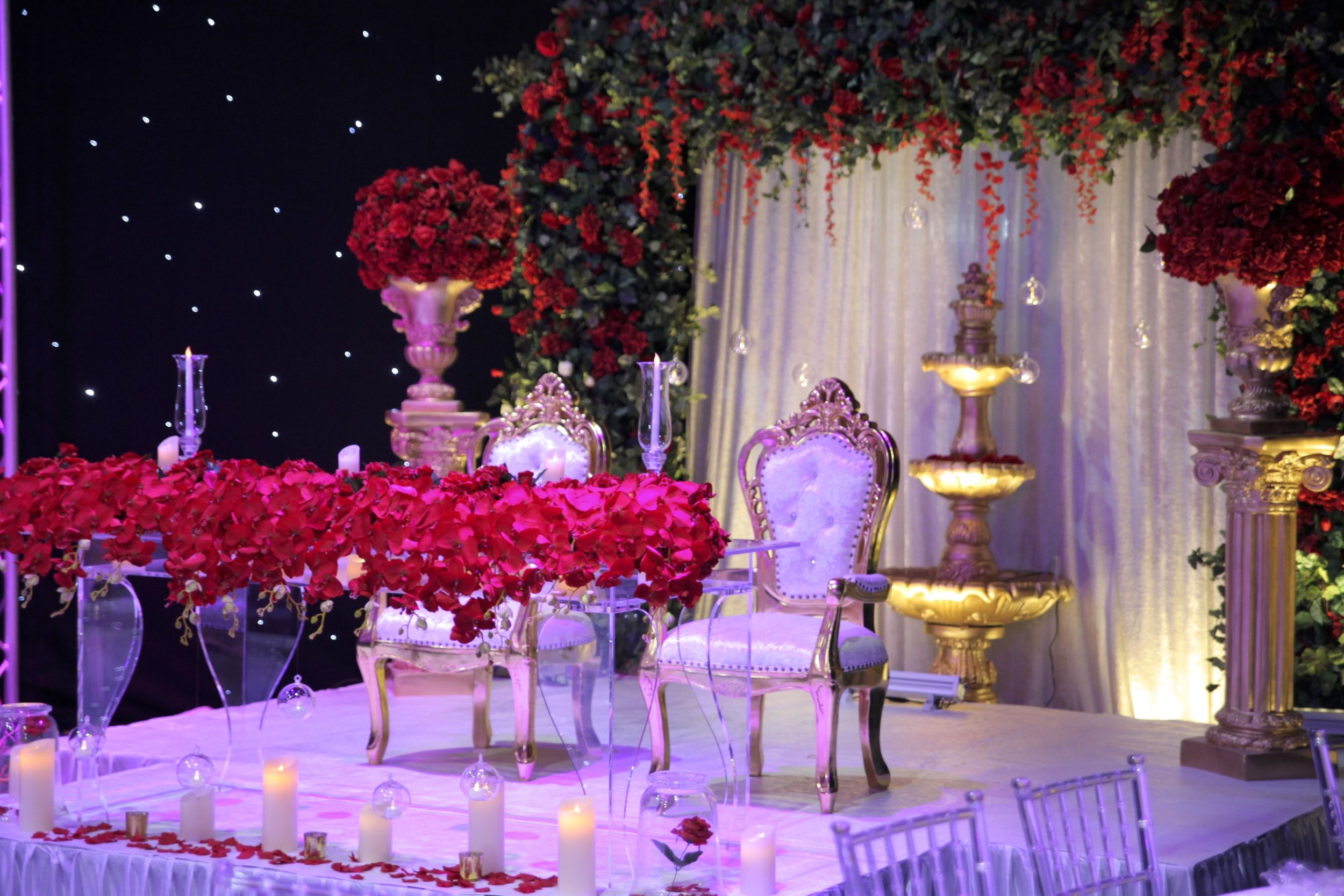 Enchanted Head Table - Our couple wanted an iconic look for their head-table. We used a transparent table to create a floating rose bush, with a custom made floral backdrop draped in red roses to complement the extravagant theme.