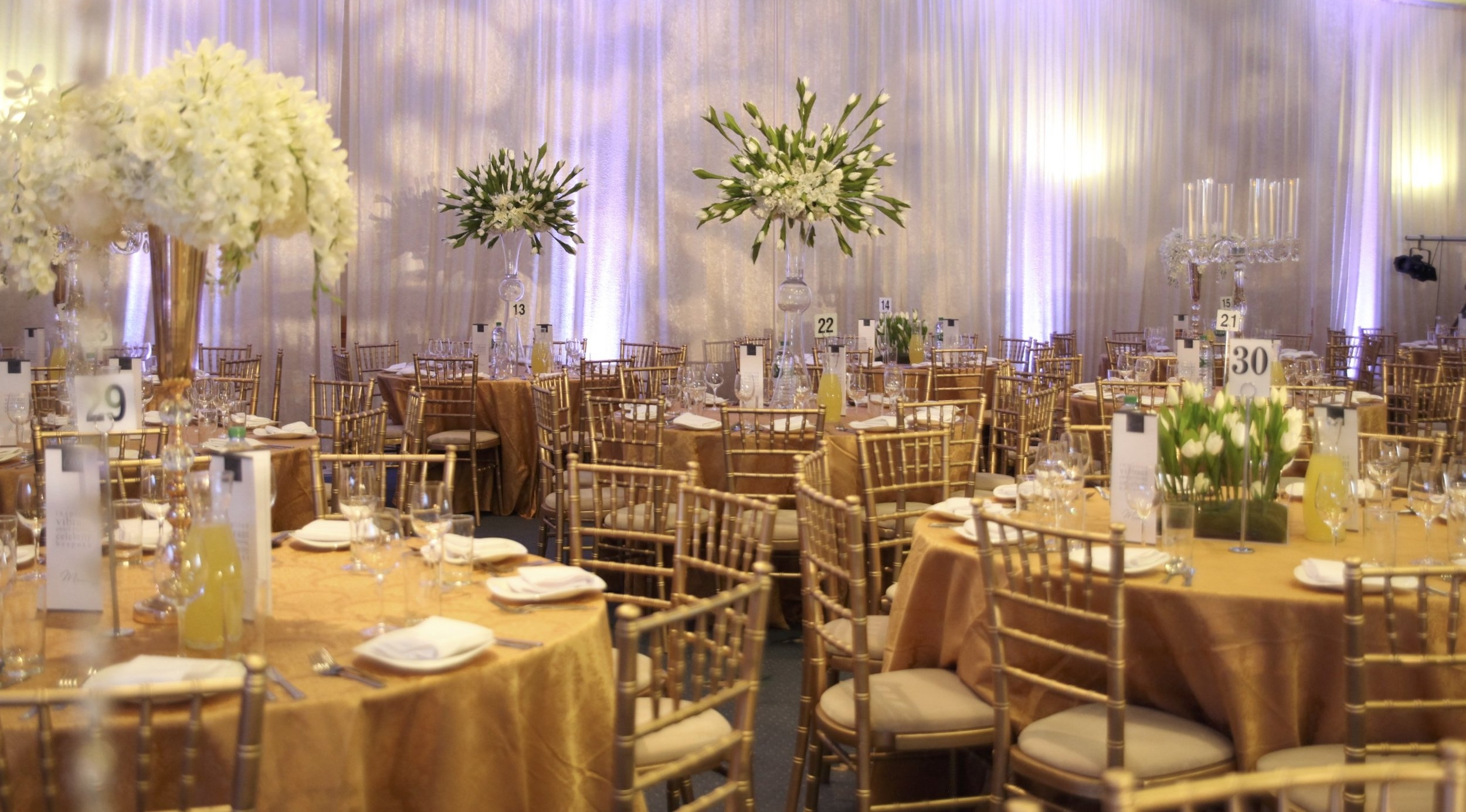 The Colour Palette - The secret to our Green Theme is using it the greens in a controlled way along with the accent golds and whites to create a classy atmosphere.We used Bespoke Venue Draping in a Ivory Crush Velour to allow for profile spot projection of patterns.