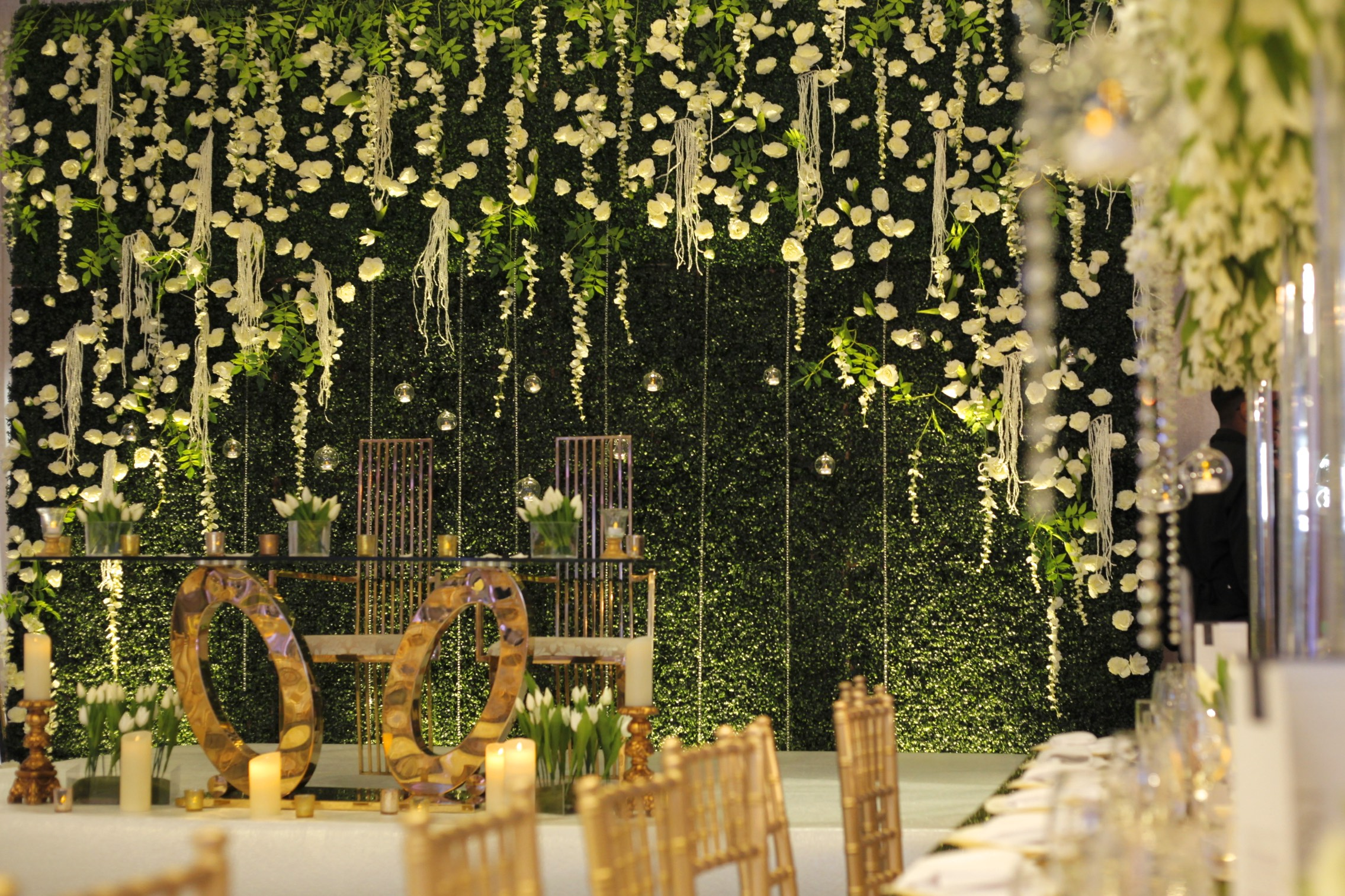 The Green Wall - The four meter High Green Wall was designed and custom built by our in-house team, following a brief of something bold, yet incorporating the floral theme used throughout the centrepieces.