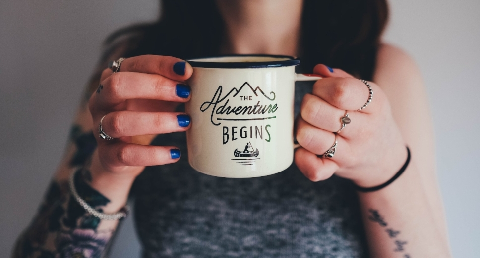 the adventure begins mug held by woman with tattoos.jpg