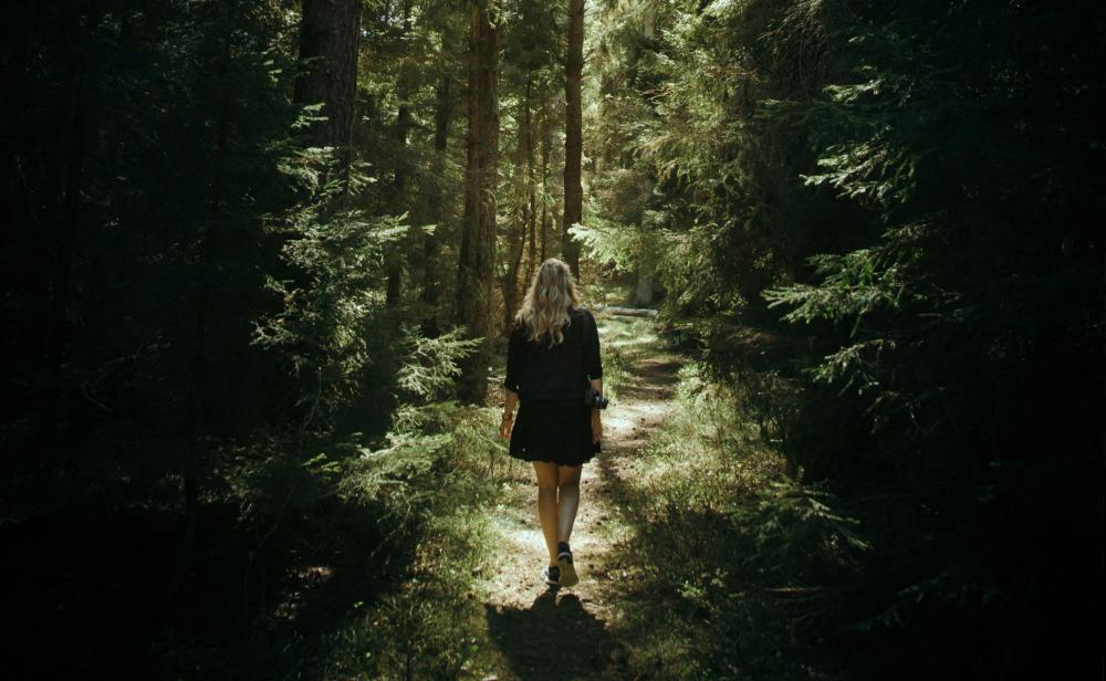 woman walking down a path through a wood.jpg