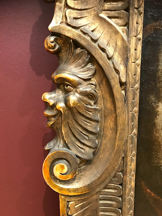 Face carved into the side of a water gilded frame.