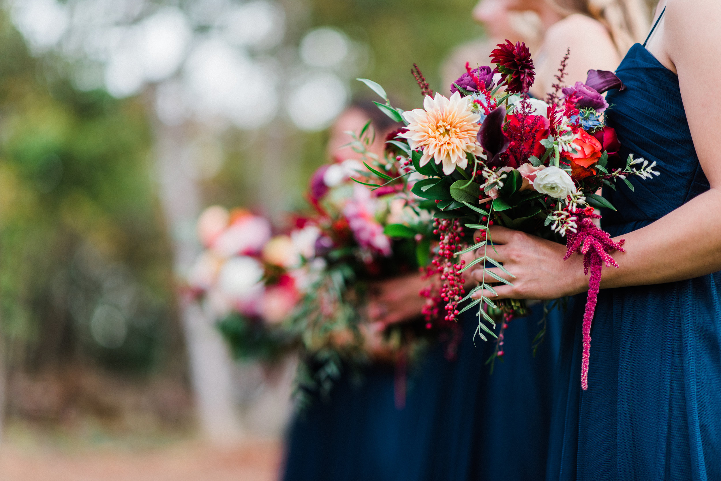 Burgundy, plum and soft gold flowers pop against these navy bridesmaids' dresses. Photo:  Rebecca Ames Photography .