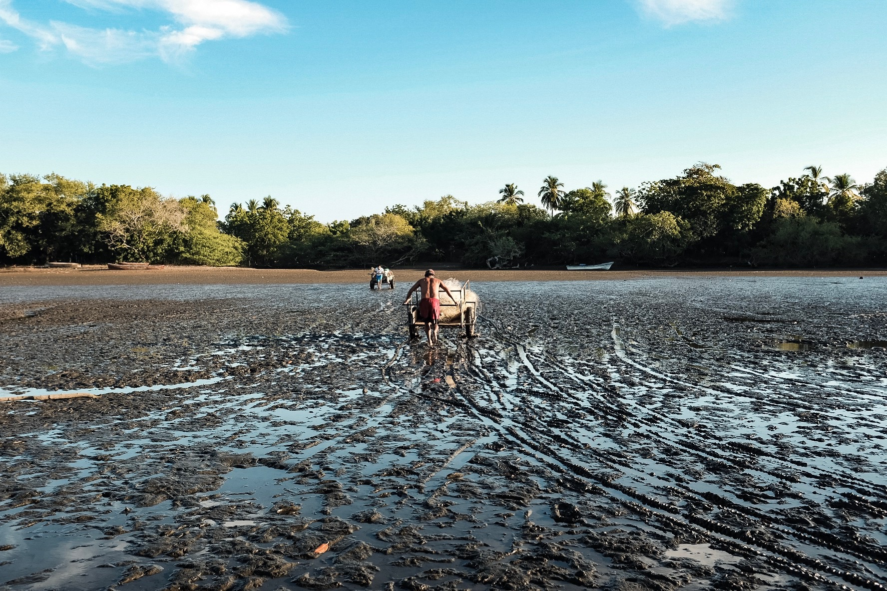 A man hauls a used net back to shore.