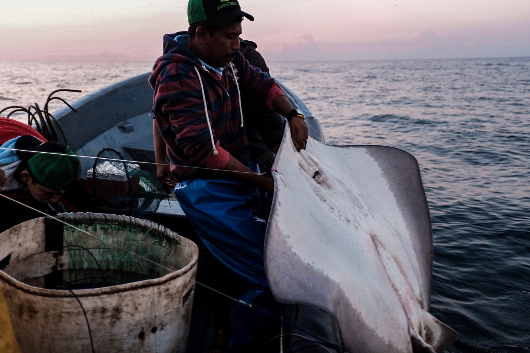 """The Fish"" - In a marine landscape scarred by blasts, few fish remain to be caught. So now stingrays are hooked and hauled, thrashing and flailing frantically out of the water. Their fins are sliced off and sold as imitation shark fin. Despite the scarce haul, the captain distributes most of the fish to the men who helped load the boat the night before."