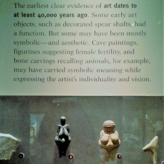 Placards that speak to the origins of art, what sets us apart from other creatures is SYMBOLIC thinking and forms of communication. ART is our unique contribution to the universe. Also, much love for the  Woman of Willendorf , shown here in facsimile, in a reddish-brown cast, a 30,000 year old rendering of the Goddess.