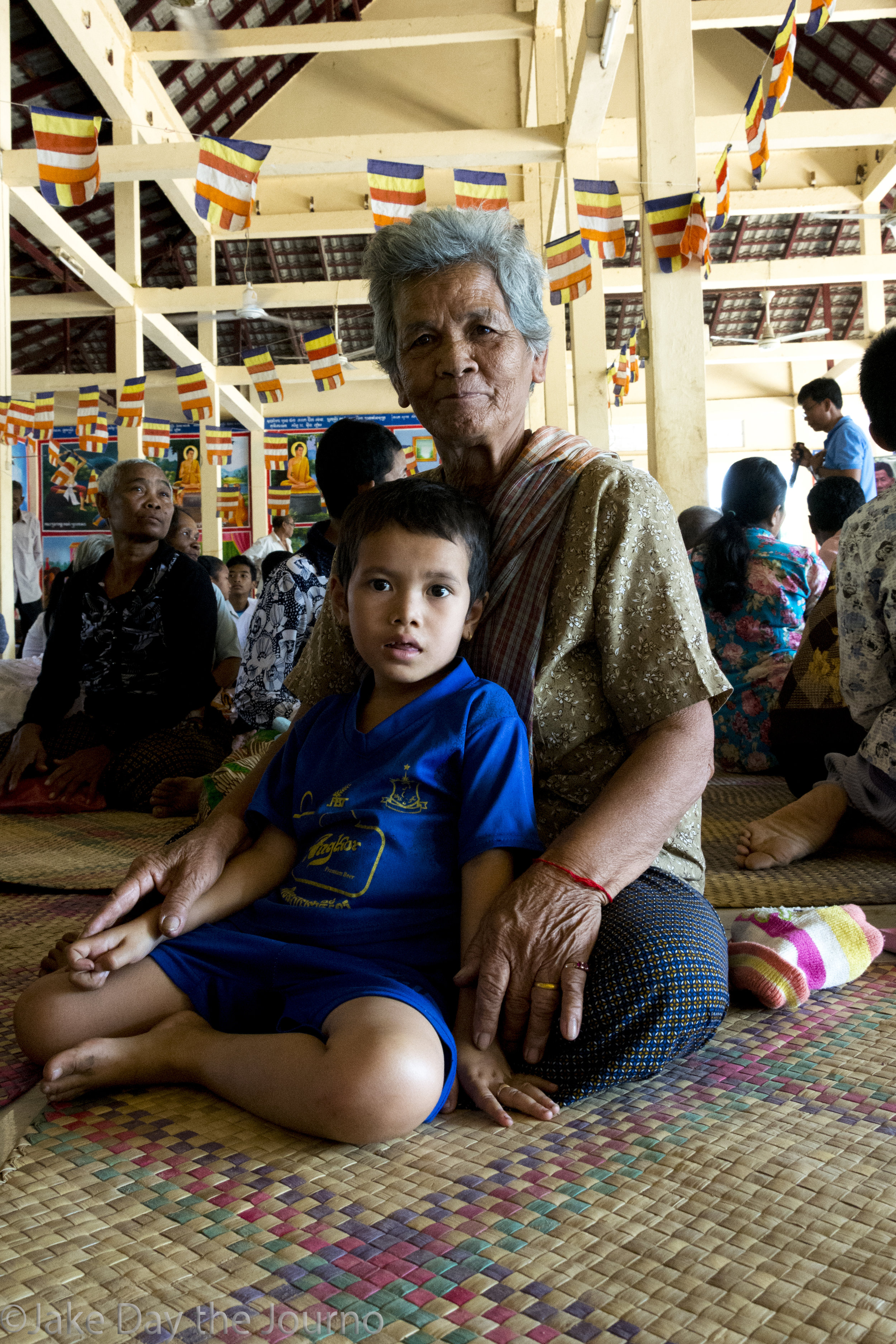 Prak Imm, 77, and her grandson wait for the testimonial ceremony to begin, organised by the Transcultural Psychosocial Organisation for the 'Healing and Reconciliation for Victims of Torture of Khmer Rouge Trauma' program at Ta Ann village, Ta Ann commune, Kralanh district, Siem Reap province on 18/01/18 by Jake Day. The ceremony brings the young and the old together to heal old wounds and pass on history.