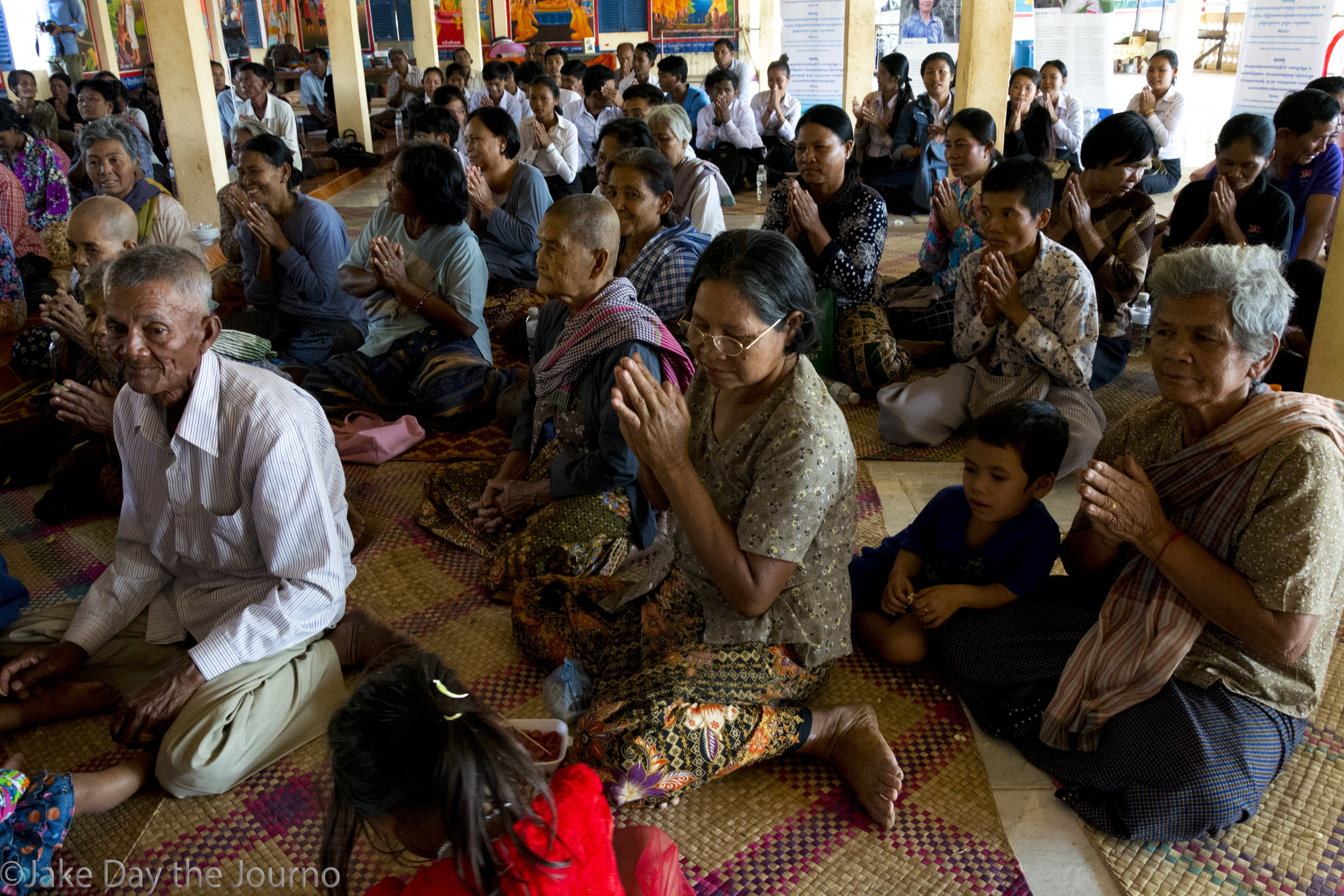 Members of the Ta Ann commune pray during a testimonial ceremony organised by the Transcultural Psychosocial Organisation for the 'Healing and Reconciliation for Victims of Torture of Khmer Rouge Trauma' program at Ta Ann village, Ta Ann commune, Kralanh district, Siem Reap province on 18/01/18 by Jake Day. Members of the Ta Ann Commune and local school children come to the ceremony to witness the survivors testimonies.