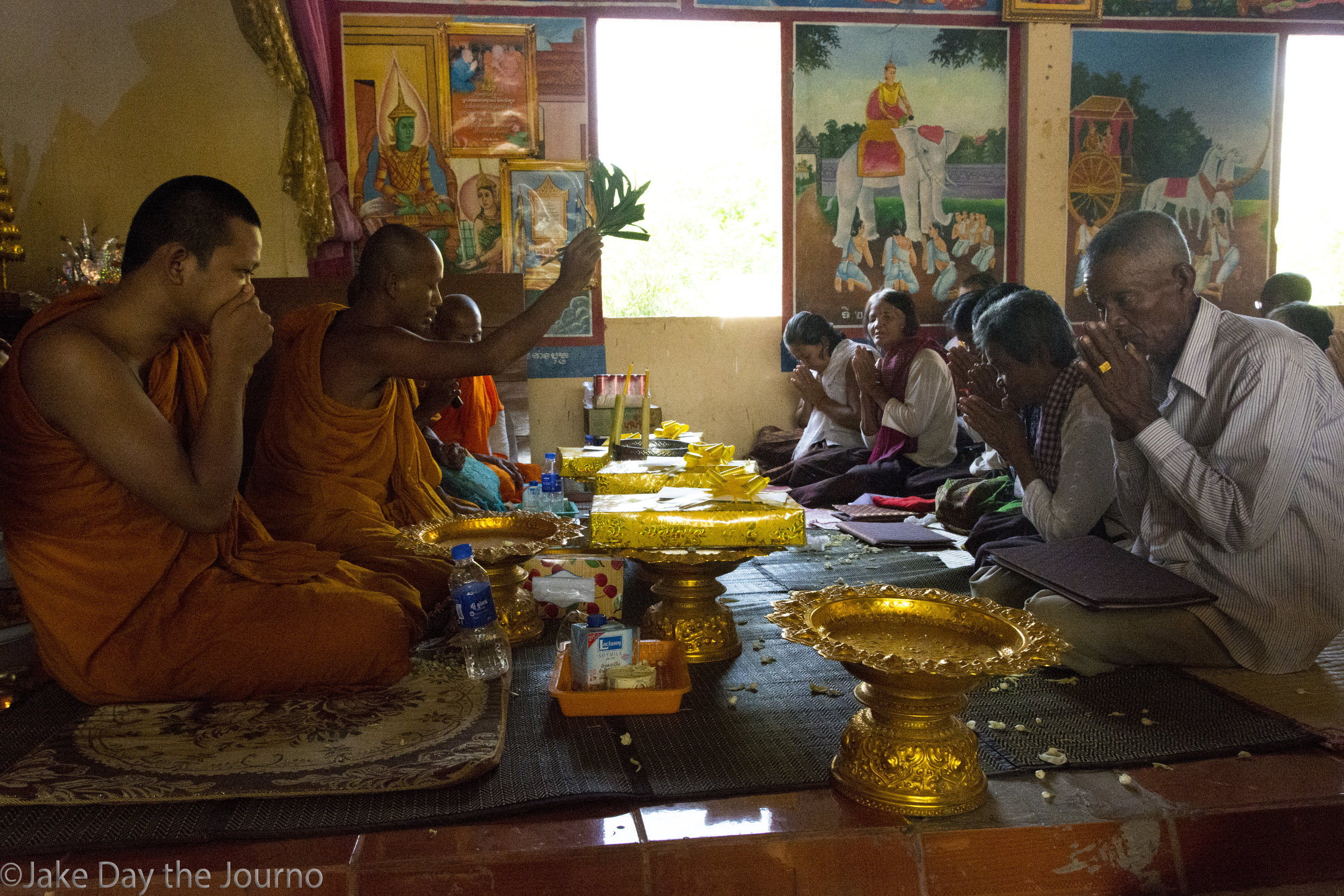 Monks Soeuy Boeurn, 18, Ply Louhong, 38, Chhun Da, 44, and Leourm Hem, 87, give blessings to survivors Theurt Thoy, 54, Seaong Hiep, 65, Yim Saroeum, 64, Phang Navy, 52, Chea Noeurn, 68, and Klav Kleum, 65, during a testimonial ceremony organised by the Transcultural Psychosocial Organisation for the 'Healing and Reconciliation for Victims of Torture of Khmer Rouge Trauma' program at Ta Ann village, Ta Ann commune, Kralanh district, Siem Reap province on 18/01/18 by Jake Day.