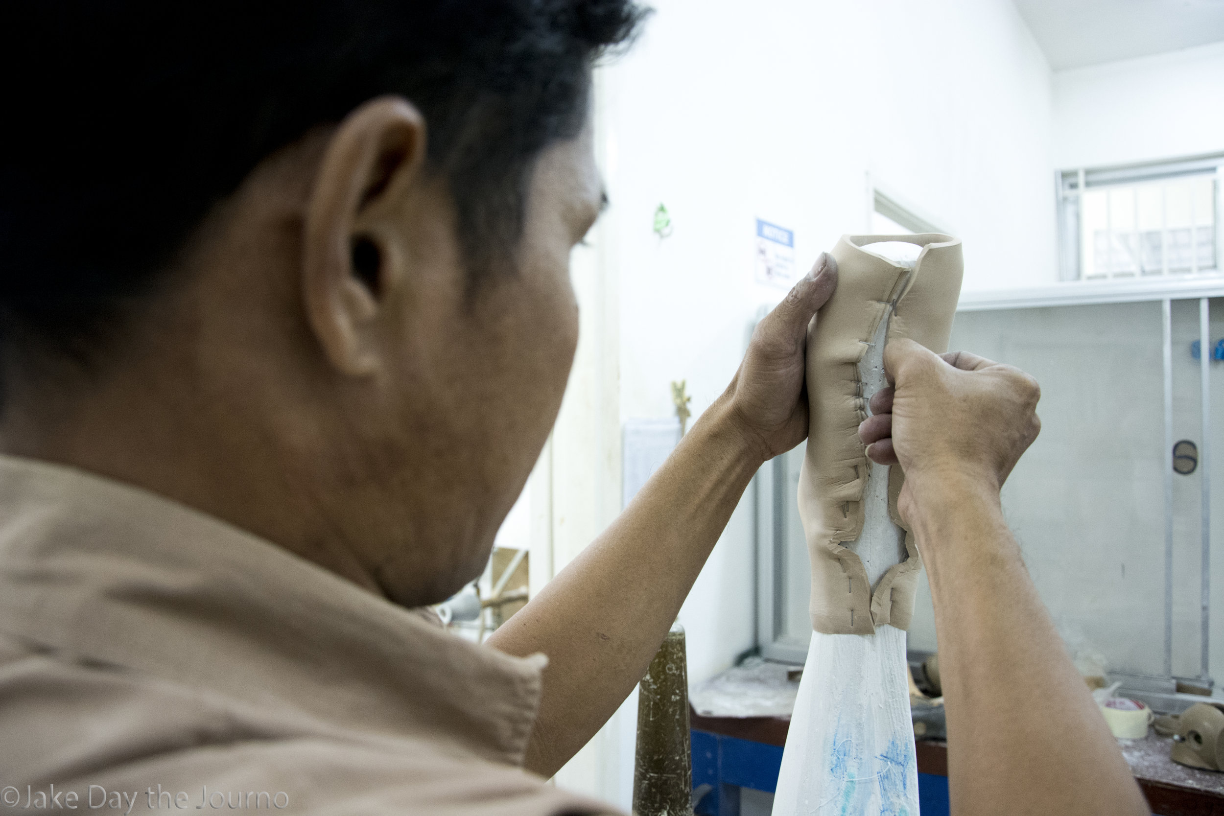 A staff member staples plaster to a mould at the Exceed Cambodian School of Prosthetics and Orthotics on 15/01/18 by Jake Day. The School of Prosthetics and Orthotics run a clinic that provides prosthetics and orthotics for Cambodians with physical disabilities.