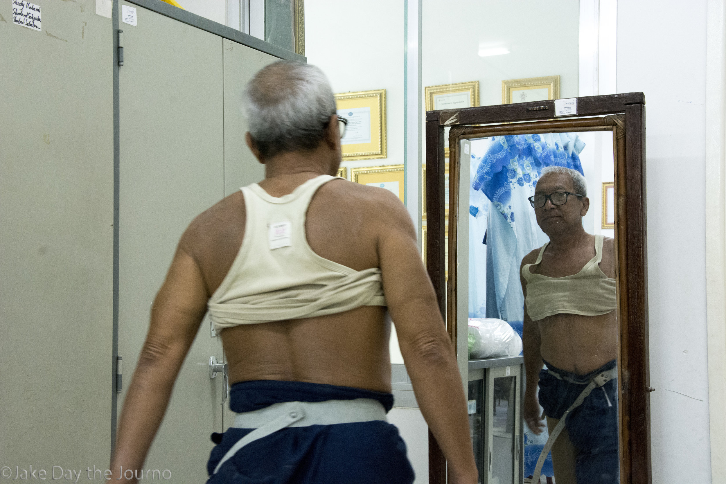 Chim Samang, 60, sizes himself in a mirror during gait testing at the Exceed Cambodian School of Prosthetics and Orthotics on 15/01/18 by Jake Day. Mr Samang lost his leg after stepping on a landmine in 1986 when he was a soldier.