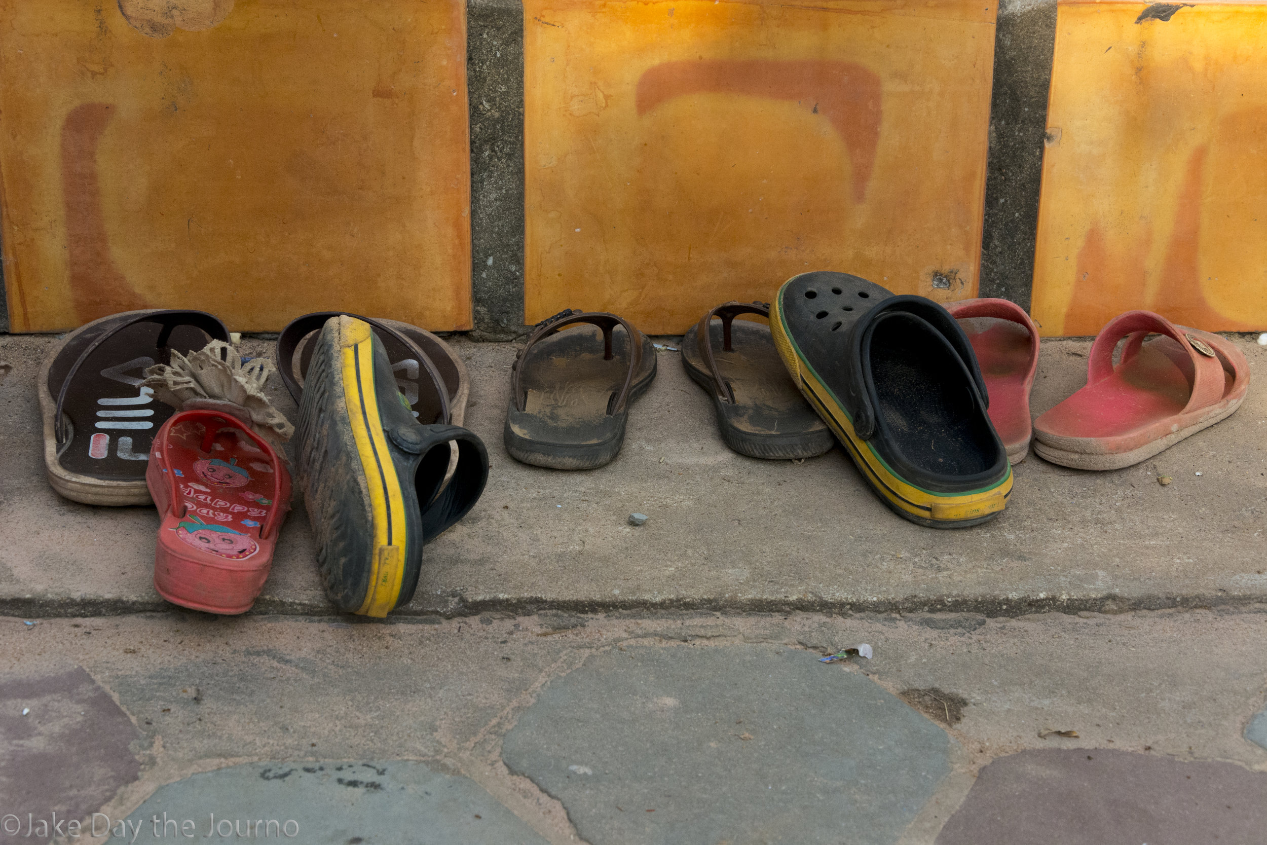 Childrens shoes line the pavement outside classrooms at Savong's School, Don Teav Village, on 25/01/18 by Jake Day.