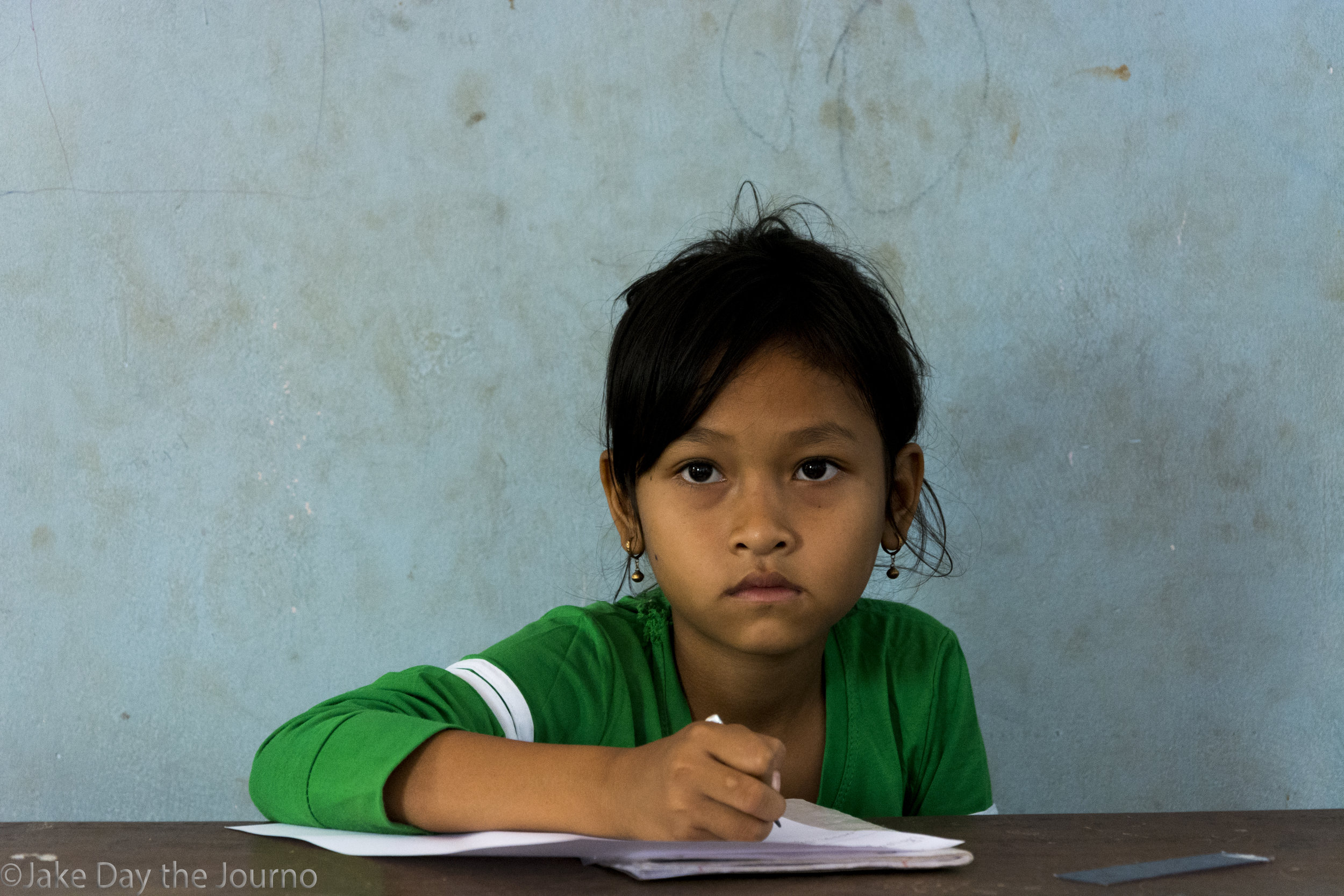 Vann Ta listens attentively during English class at Savong's School, Don Teav Village, on 25/01/18 by Jake Day. Savong's School is a small school with run-down facilities due to a lack of funding. There are only two classrooms, one computer room, a library, a teacher's lounge, and a field where the children play soccer.