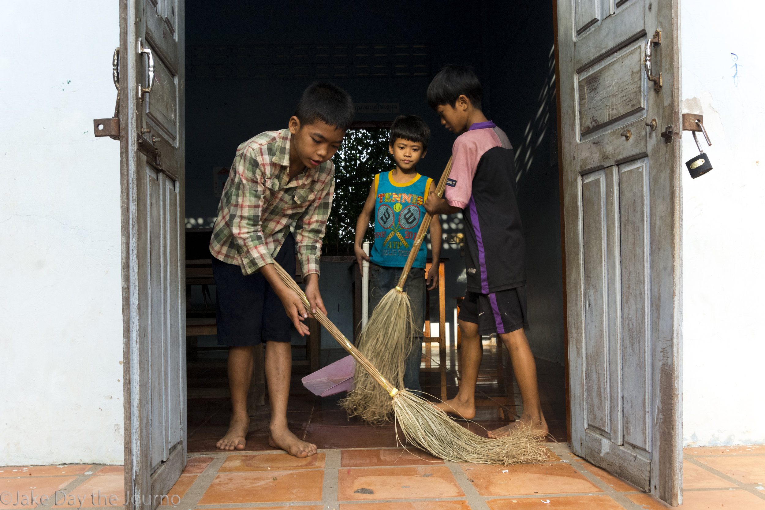 Makara, 12, Fieyok, 10, and Vihyo, 11, sweep the classroom before class at Savong's School, Don Teav Village, on 25/01/18 by Jake Day. The students that arrive early sweep the school every morning before class.