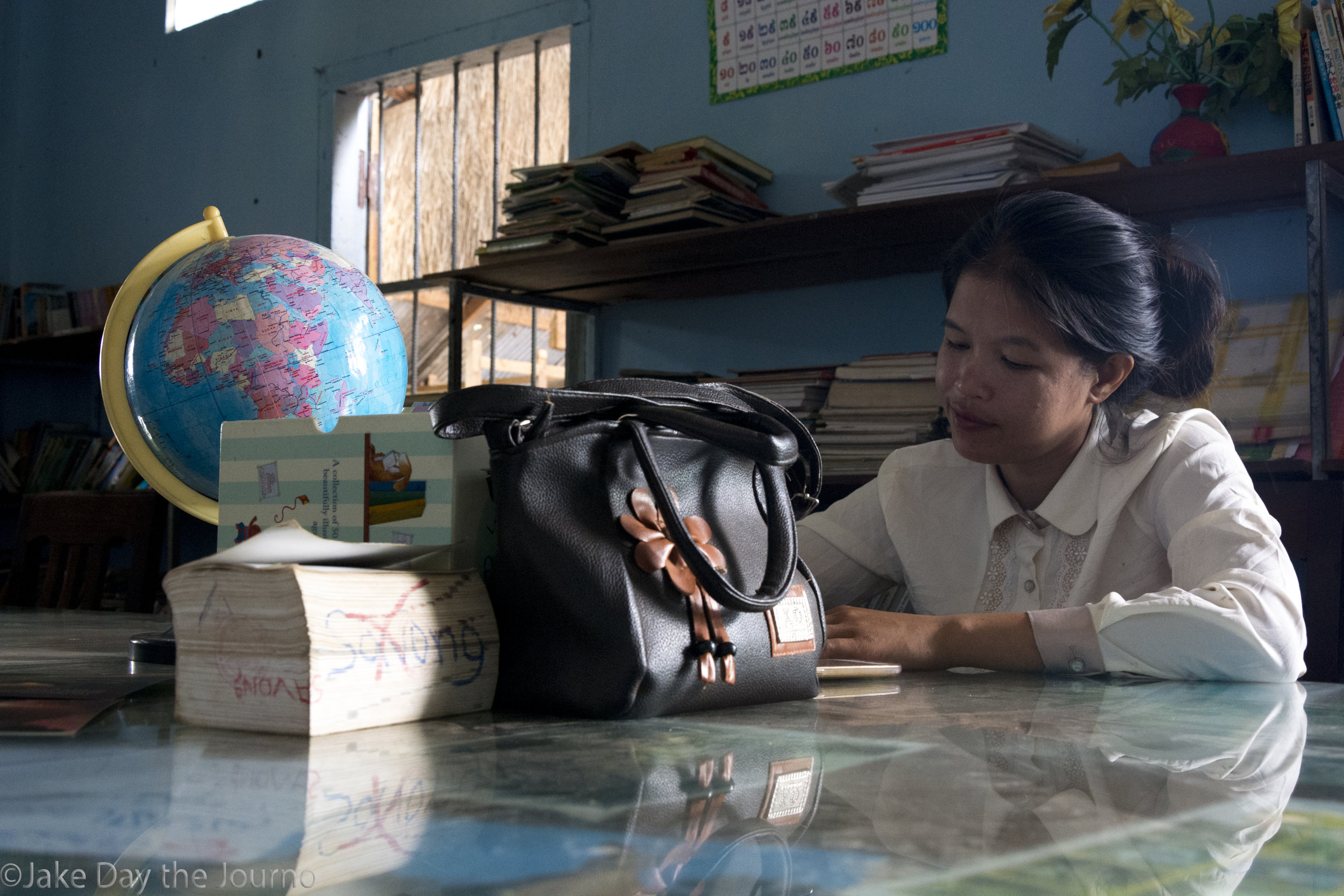 Librarian Sray Lam, 28, reading a book at Savong's School, Don Teav Village, on 24/01/18 by Jake Day.