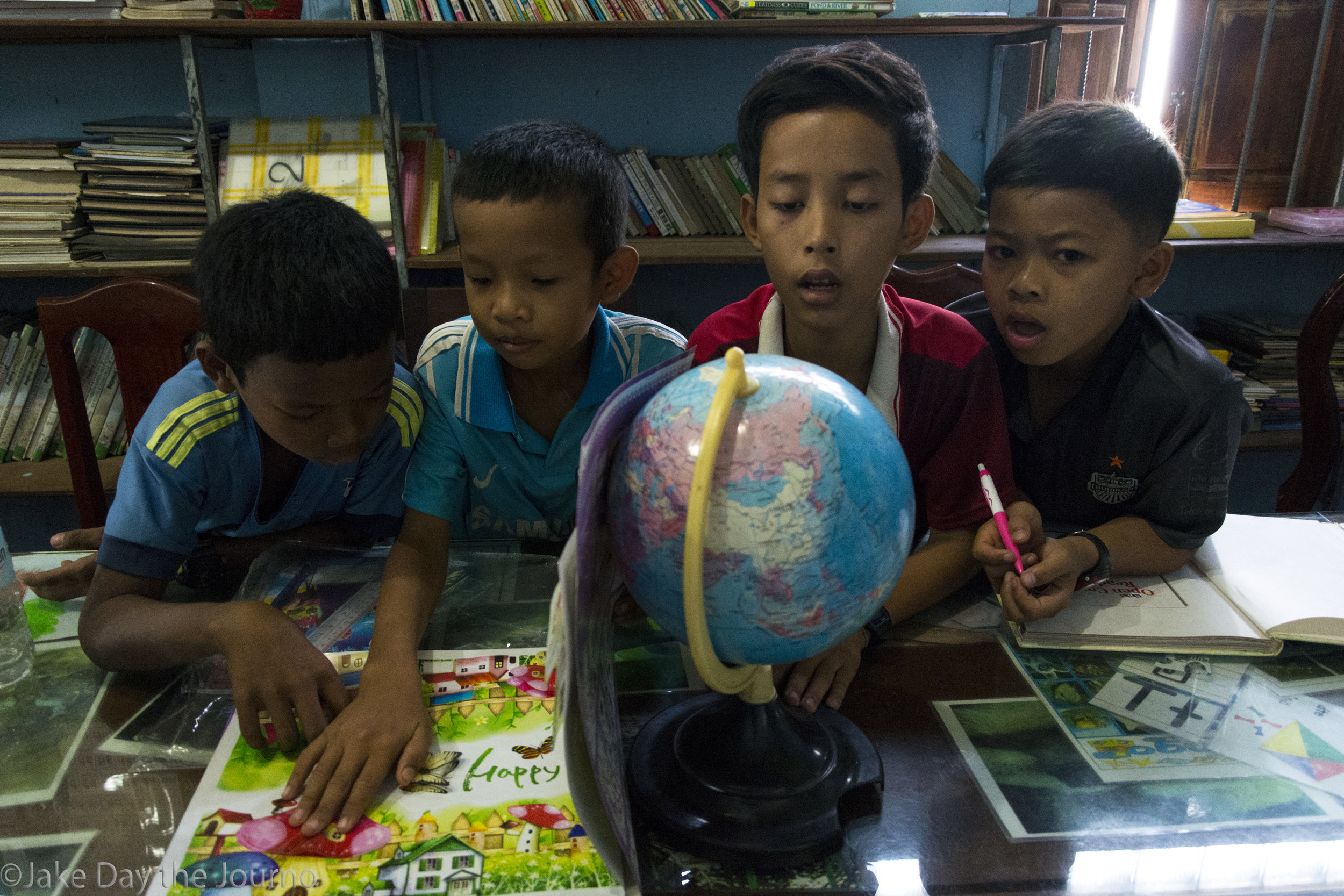 Movmab, 12, Lepeang, 12, Vicheka, 13, and Pheaktra, 12, study a globe in the library at Savong's School, Don Teav Village, on 25/01/18 by Jake Day.
