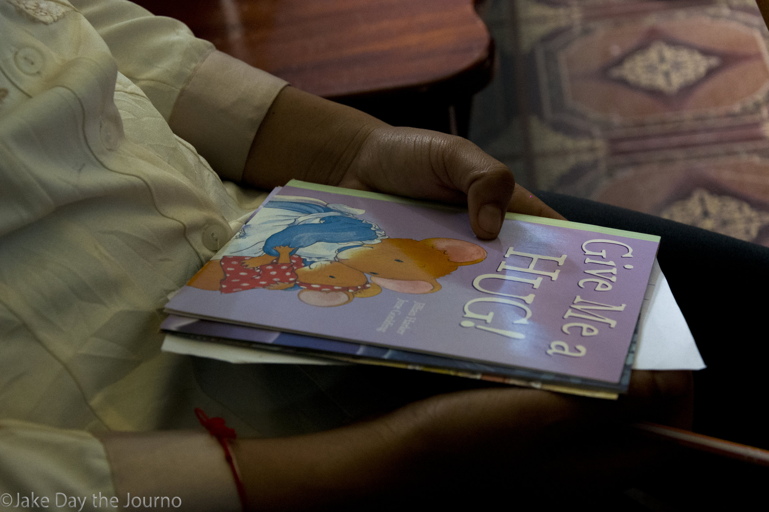 Librarian Sray Lam, 28, tentatively holds a childrens book at Savong's School, Don Teav Village, on 24/01/18 by Jake Day.