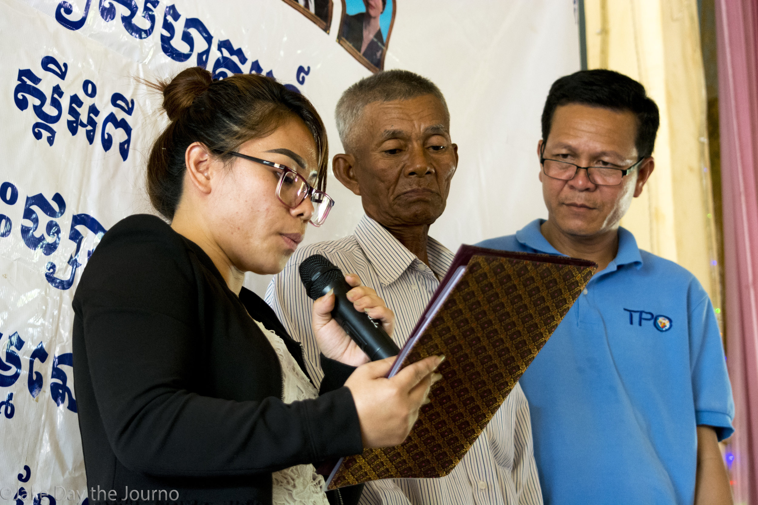 Counselors Sonary Chor and Sang Seum surround Klav Kleum, 65, for support during a testimonial ceremony organised by the Transcultural Psychosocial Organisation for the 'Healing and Reconciliation for Victims of Torture of Khmer Rouge Trauma' program at Ta Ann village, Ta Ann commune,Kralanh district, Siem Reap province on 18/01/18 by Jake Day. Sonary Chor reads Klav Kleum's testimony to members of Ta Ann village while Sang Seum stands by to comfort Mr Kleum.