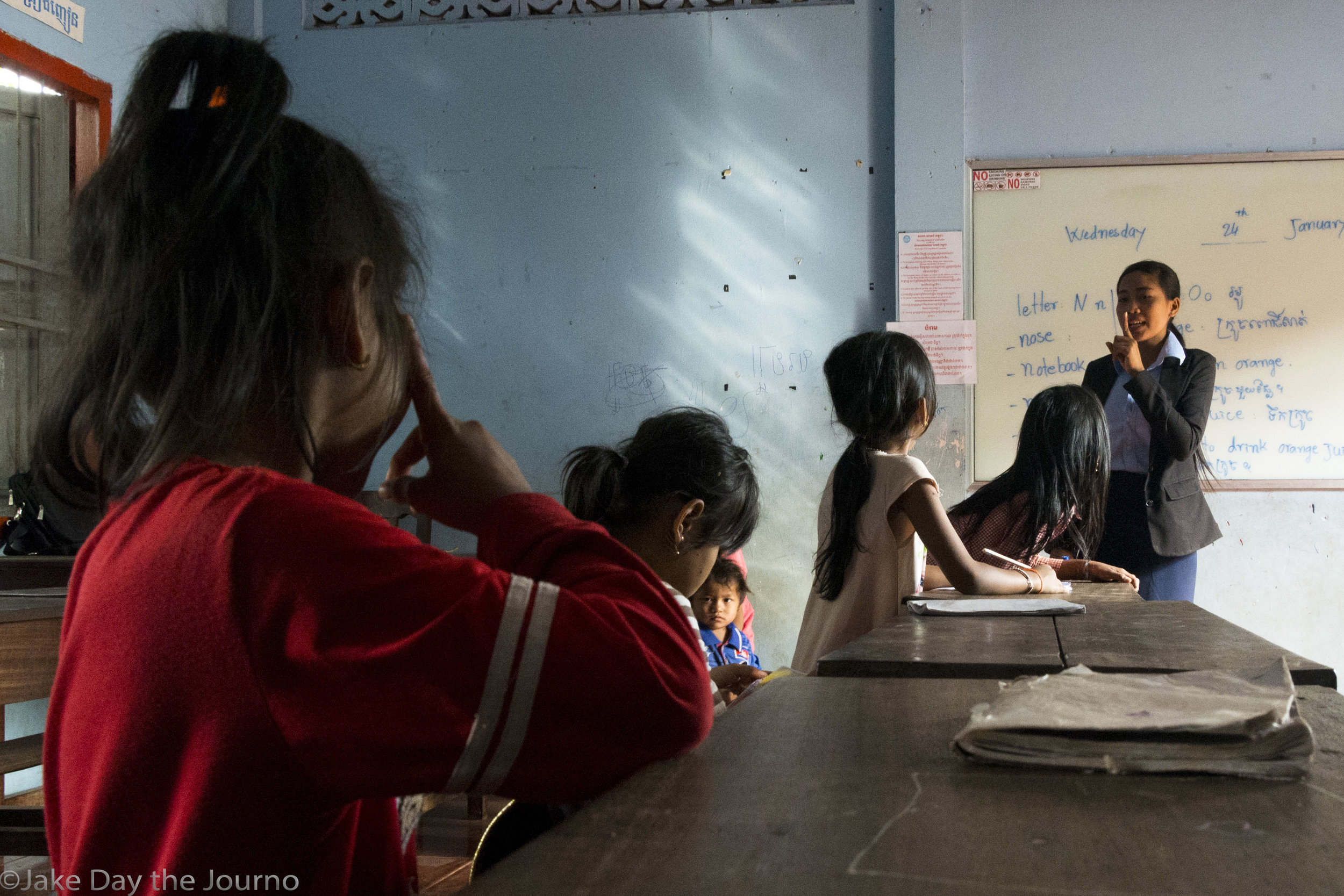 Four students are hushed by their teacher, Chuun Savy, 19, at Savong's School, Don Teav Village, on 24/01/18 by Jake Day.