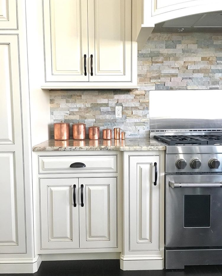 Modern farmhouse kitchen with stone backsplash, white cabinets and copper antique canisters.