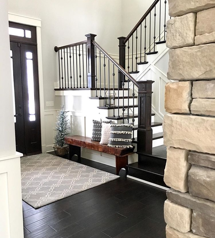 Modern farmhouse foyer with wainscoting, oversized front door, stone wall and antique bench.