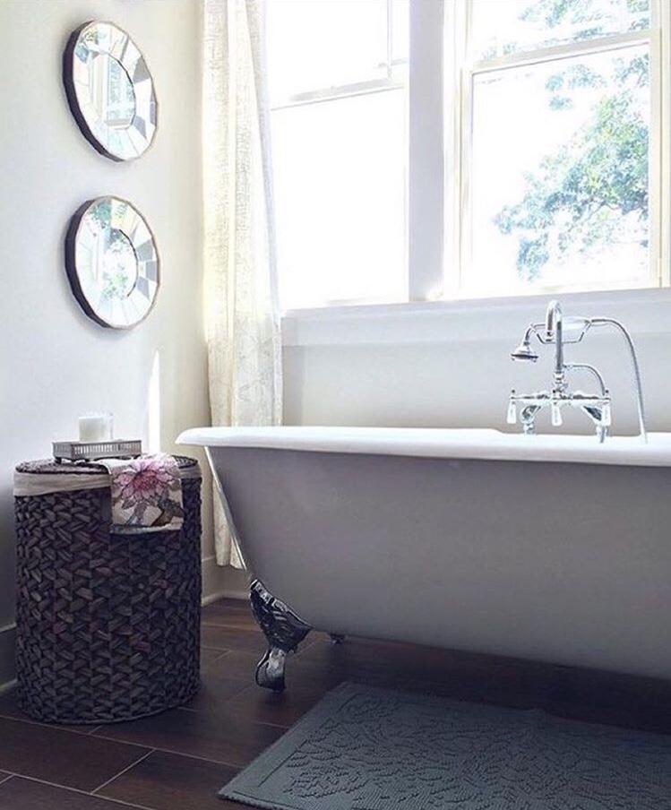 Modern farmhouse bathroom with clawfoot tub and mirror wall.jpg