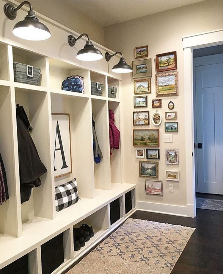 Modern farmhouse mudroom with vintage rug, gallery wall and neutral built-ins painted with Sherwin-Williams Antique White.