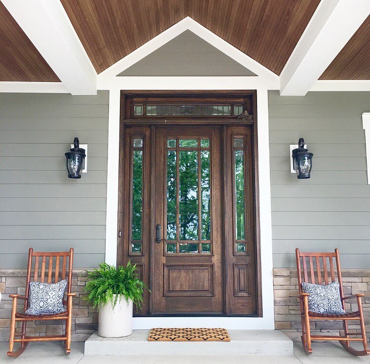 Modern farmhouse front porch with rocking chairs, green-gray painted siding and stained doors.