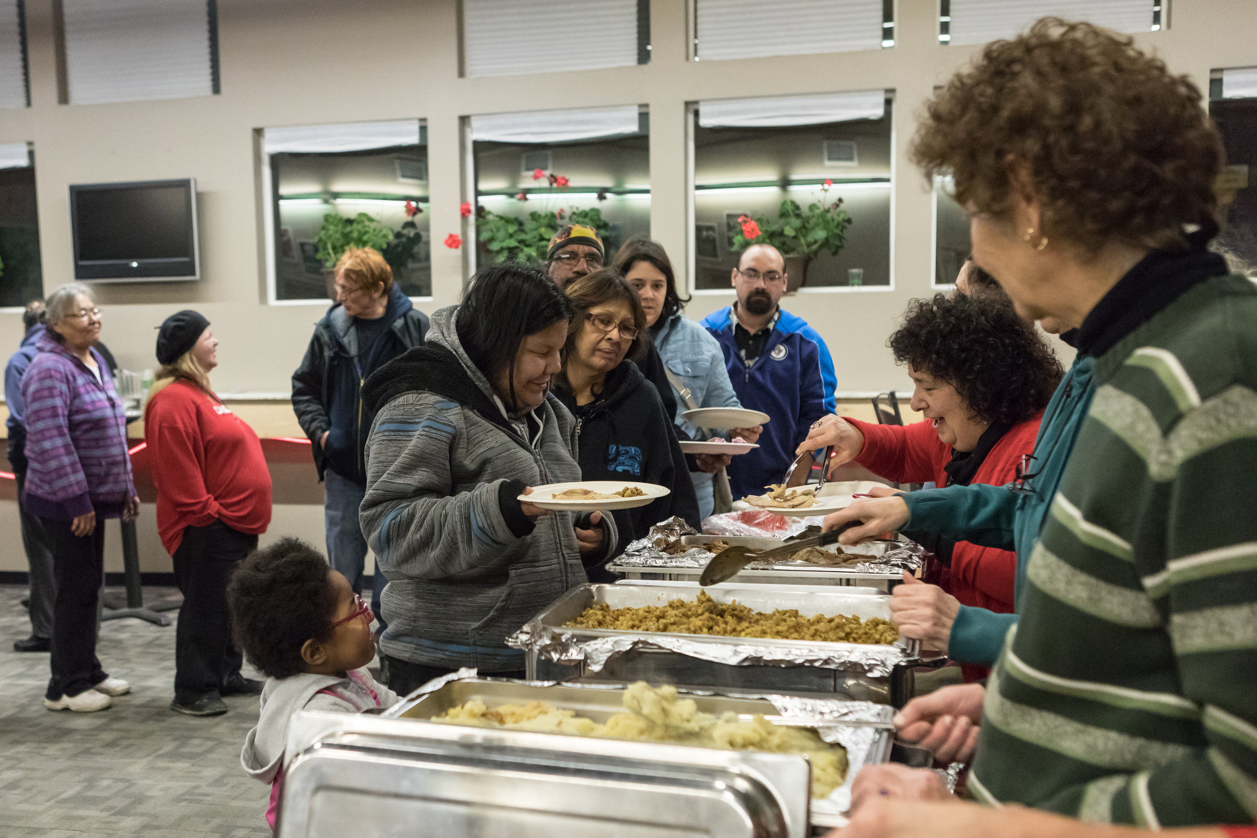 Volunteers serving dinner to guest at the annual Holiday dinner. [2017]