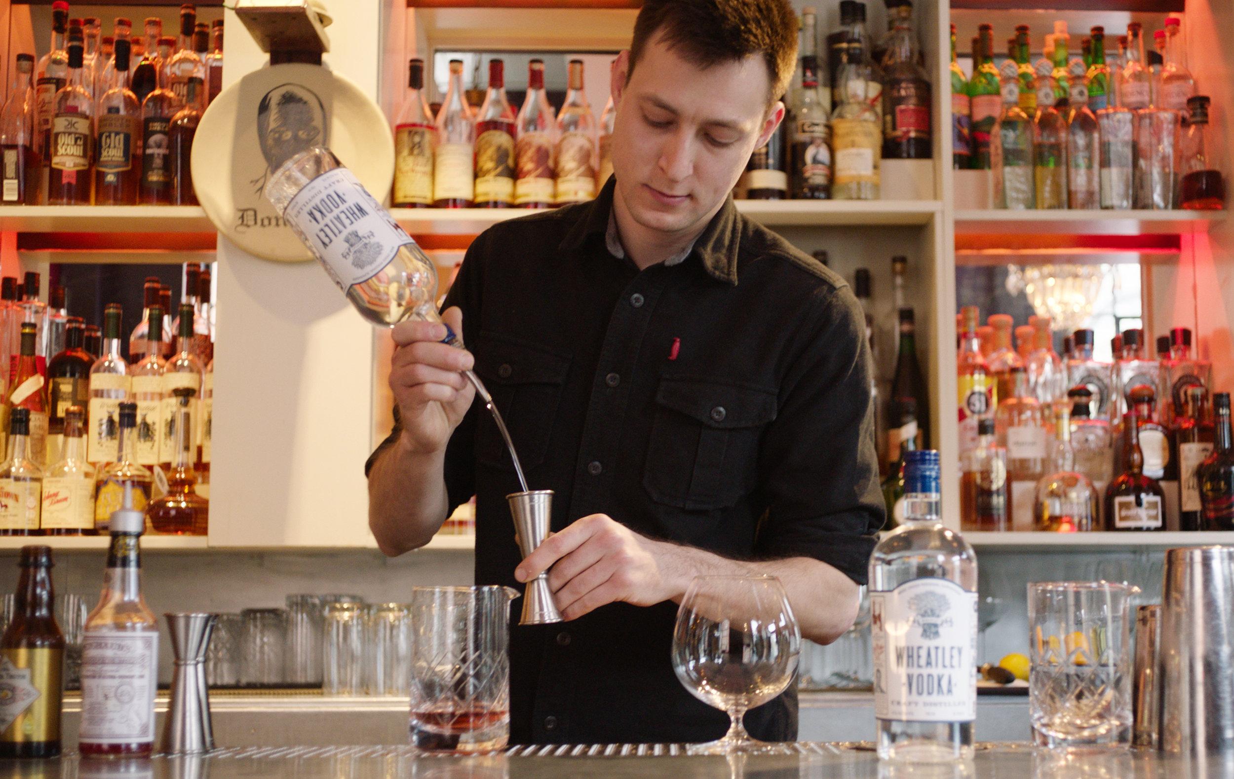Proof on Main Bartender Greg Galganski standing behind his bar preparing a cocktail with Wheatley Vodka.