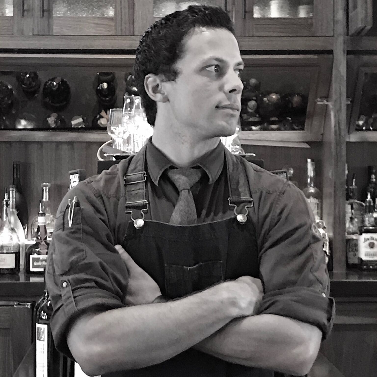Black and white photo of Bartender Tanner Johnson standing in front of his bar with his arms crossed looking off camera.