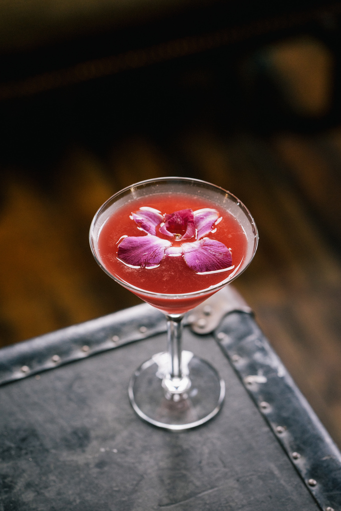 Red colored cocktail in a martini glass garnished with an orchid.