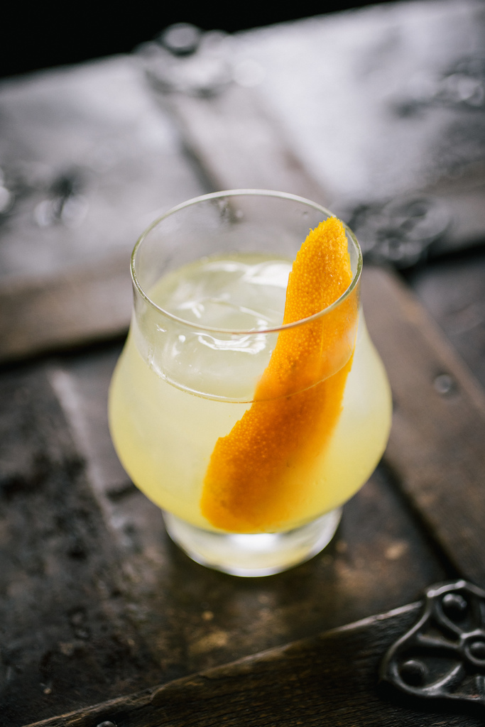 Refreshing cocktail with an orange peel.