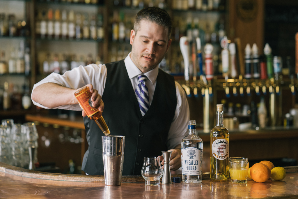 Bartender Jason Curtsinger from Belles Cocktail House pouring bitters into a mixing glass to make a cocktail featuring Wheatley Vodka.