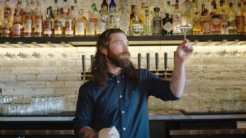 Matthew Wesolik, a bartender at Clever Rabbit, standing behind his bar looking into the camera with a focused expression.