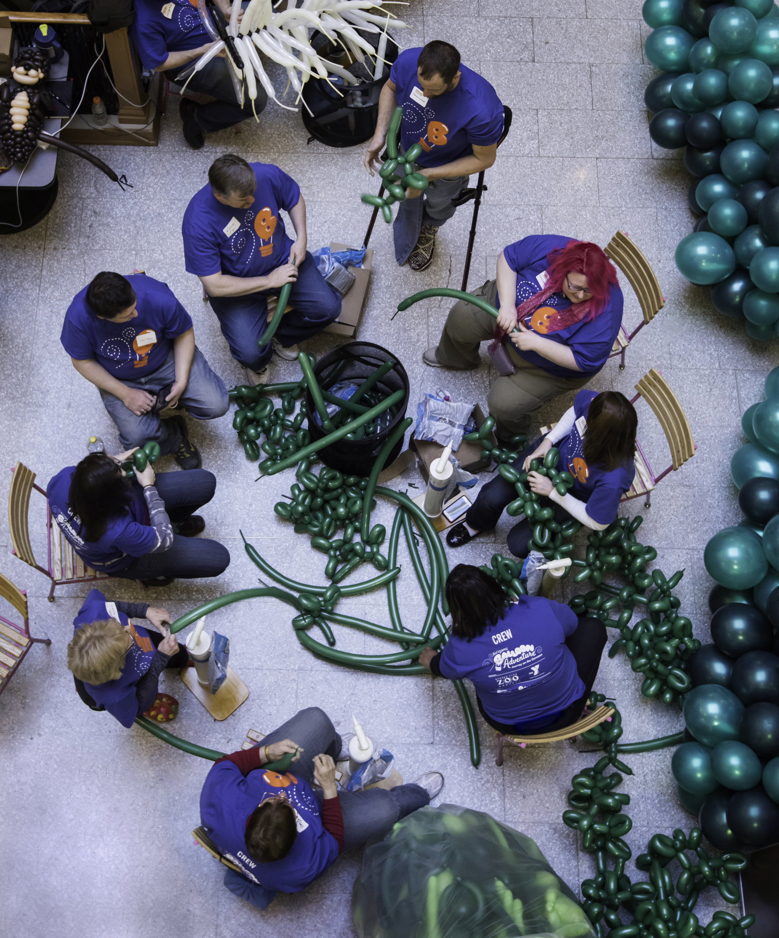 """Volunteers from around the country and the world work on the installation. // University of Rochester graduate Larry Moss '92 and wife Kelly Cheatle work on """"Airigami Balloon Adventure: Journey on the Genesee,"""" a five-story, 50-foot sculpture made from more than 40,000 compostable balloons at the Sibley Building atrium in Rochester, NY January 28, 2016. // photo by J. Adam Fenster / University of Rochester"""