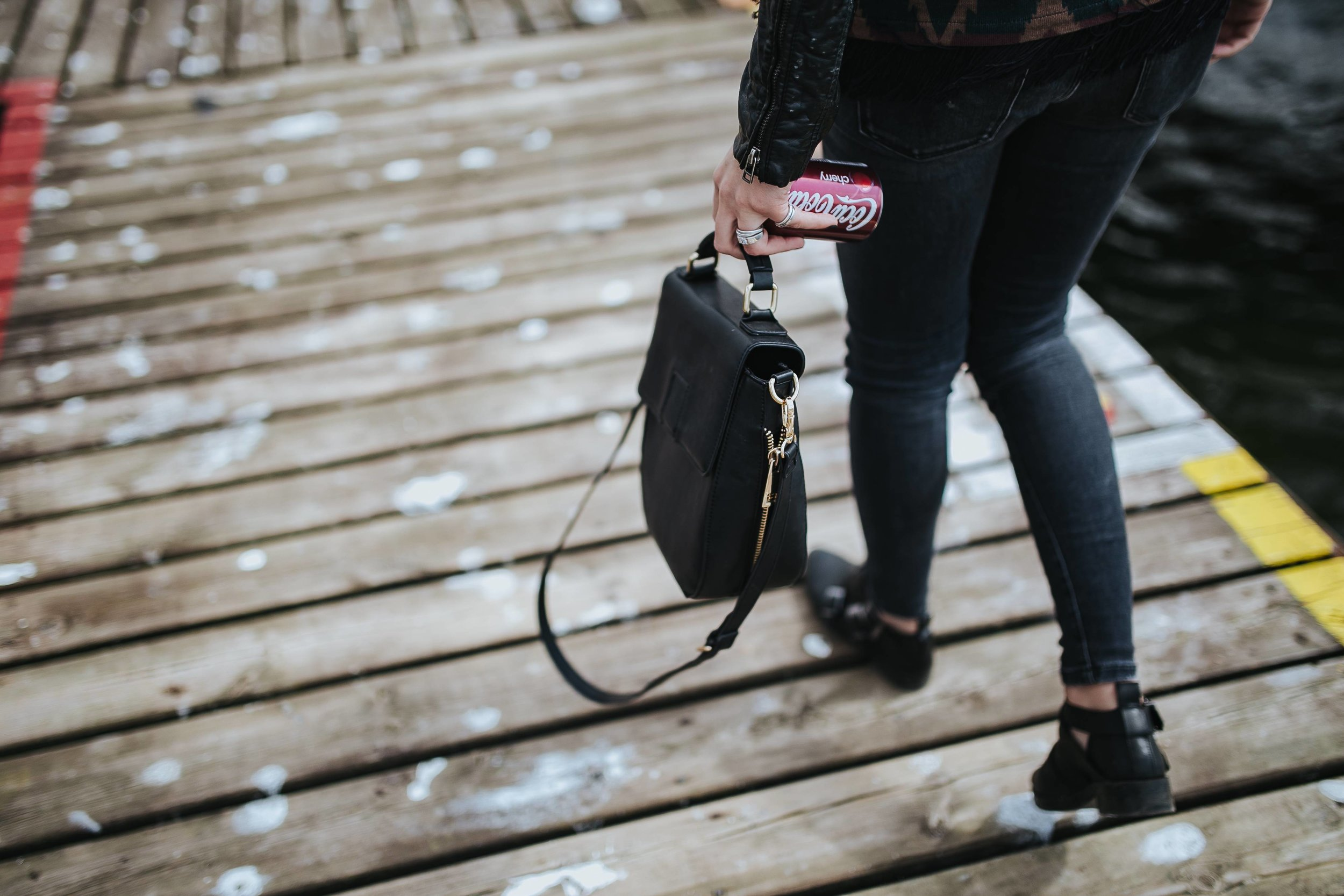 kaboompics_Woman with a black bag and a can of coke walking on a wooden pier.jpg