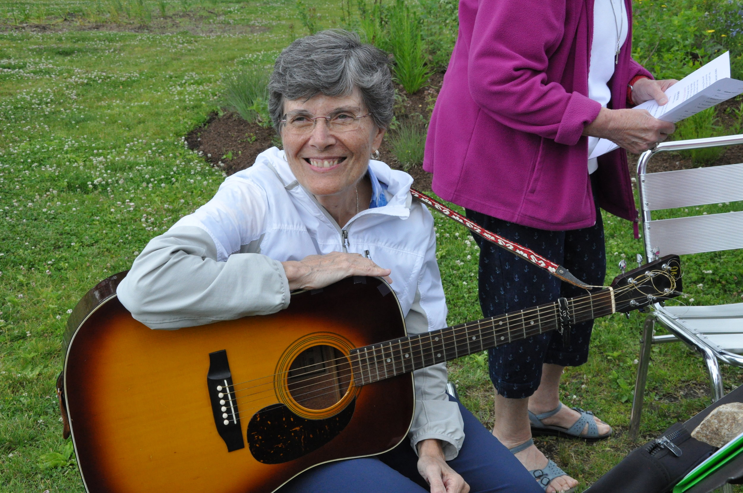 Sister Ines Gizzarelli  playing guitar and singing during the tree planting ceremony