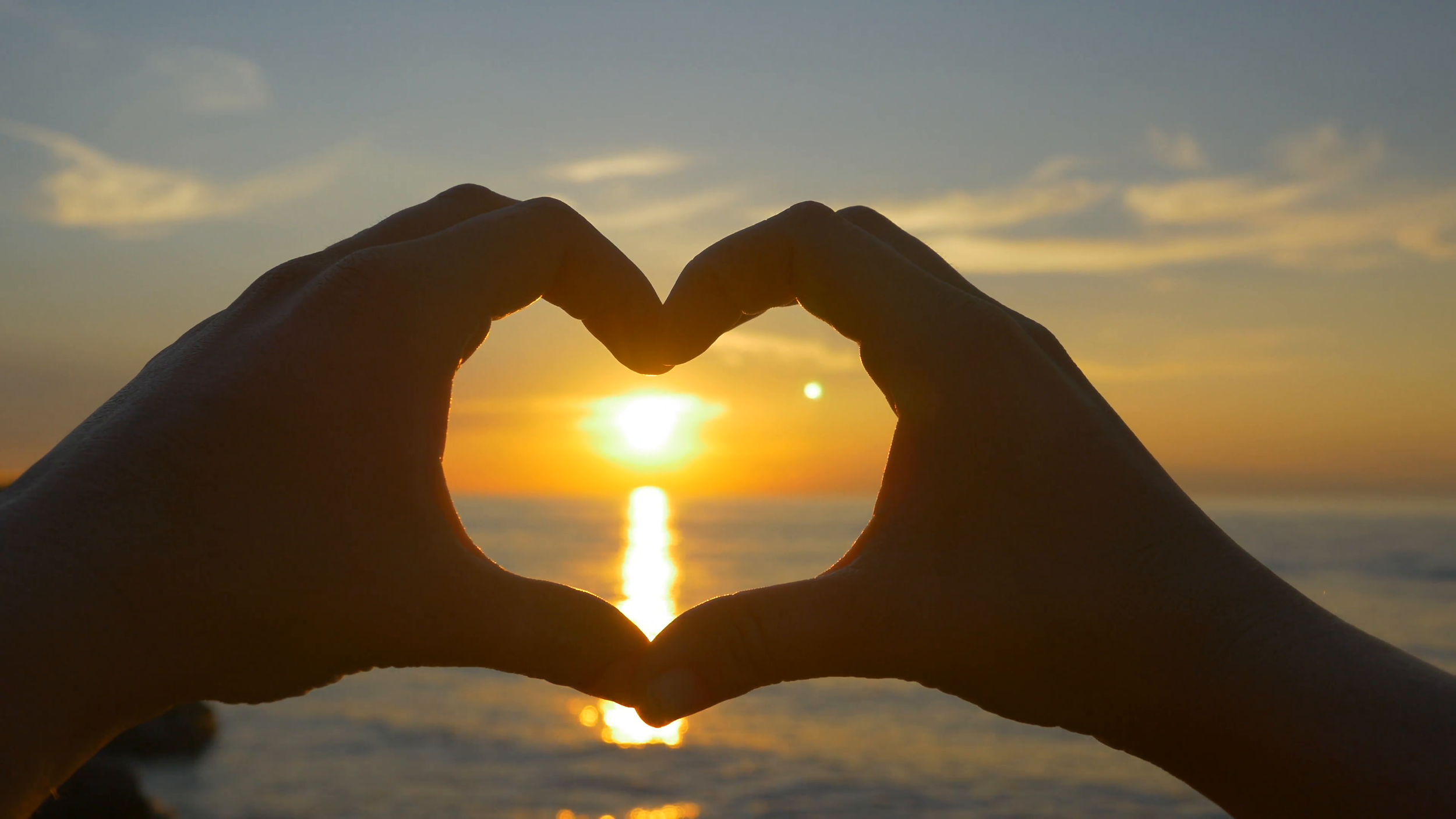 capturing-ocean-sunset-with-heart-shaped-hands_eytlelszl__F0000.png