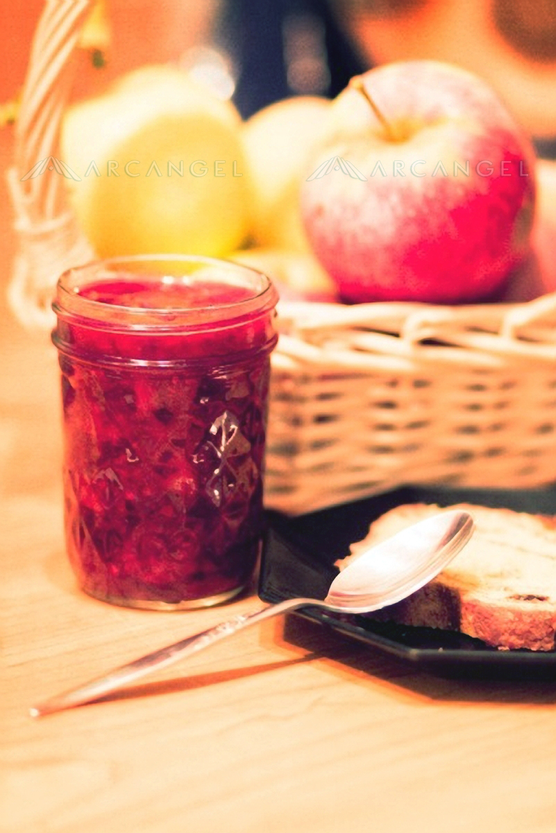 A jar of homemade jam and an uneaten piece of toast tells a different kind of story as a bountiful bowl of fruit.