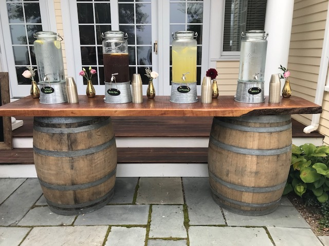 This wine barrel bar can be utilized as a bar or pictured here as a water station. This bar is about 8 feet long.