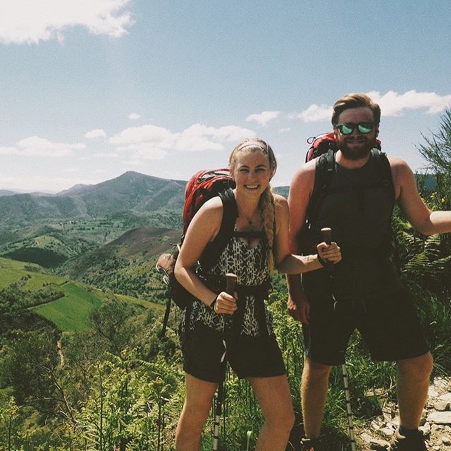 """Double tap if you think you could hike 3 weeks straight?!? I sure didn't, yet somehow, I ended up on the Camino de Santiago 4 years ago! 😅  Strolling down memory lane in my stories tonight looking back at these pics (gotta love those filters! 😂) Ty & I jokingly called this our honeymoon, even though it was about two months before our actual wedding.  To date, this is still the longest hike we've tackled - over 250 miles and 3 weeks. You better believe those packs got really light by the end as we realized how little we actually need.  This trek lit the flame for me - I've been head over heels for these long treks ever since. If I could point to where/when Unto Dust was """"born,"""" it would probably be somewhere between those hills of swishing green. 😍 . . . . . .  #hikeuntodust #untodustguides #smallinbigplaces #filmphotography #filmisnotdead #35mm #ishootfilm #35mmfilm #filmcamera #canon #canonusa #filmisalive #grainisgood #lonelyplanet #exploremore #passionpassport #visualsofearth #travelandlife #seetheworld #cntraveler #travellife #shoottoexplore #visualsoflife #tasteintravel #wildernessculture #canonusa #optoutside #getoutstayout"""