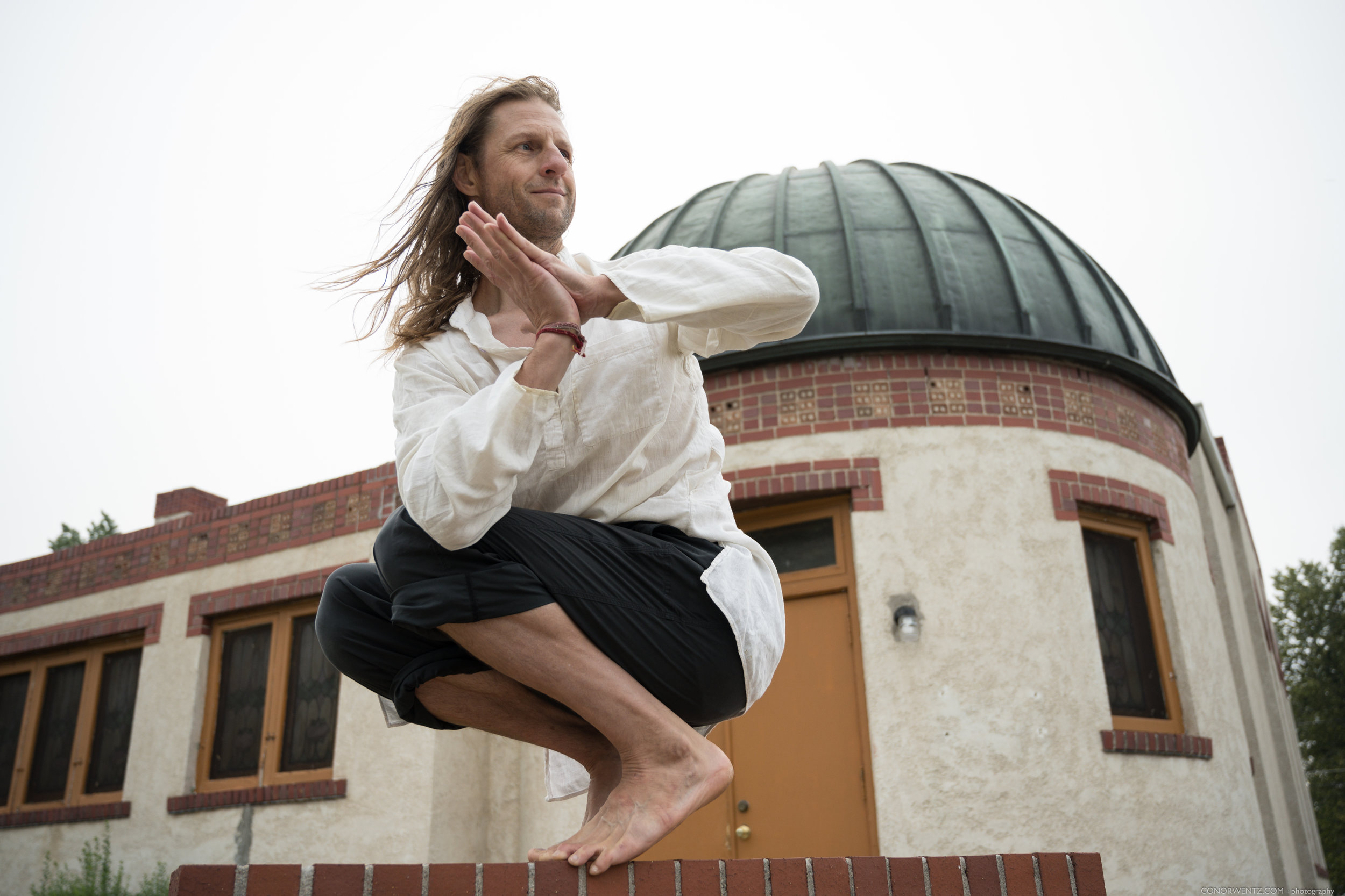"""Derik was first introduced to yoga in 1991 while on a rogue trip to India just after highschool. As he studied asana, yoga philosophy and meditated on the shores of the Ganges. A whole new world opened up inside of him and the tone for his entire adult life was set. Over the ensuing decades, he studied with world-renowned asana and meditation teachers, completed multiple 200 and 300-hour trainings, and returned to India many times to deepen his study.  He considers Baba Hari Dass and Yogarupa Rod Stryker to be his primary teachers. In 2003, he and his wife (Dr. Brenna Hatami) started   Axis Yoga Trainings   in Denver Colorado. Axis, soon to be the """"Denver Yoga Underground"""", is a school dedicated to workshops and yoga teacher trainings and is a safe haven for a diversity of people who may prefer to practice outside of a studio setting.  Personally, he believes that we each have a purpose and that life circumstances lead us an evolutionary journey to understand ourself and the role we must play. All experiences, whether """"positive"""" or """"negative"""" are an opportunity to enrich our spirit and character. Yoga aids in that process."""