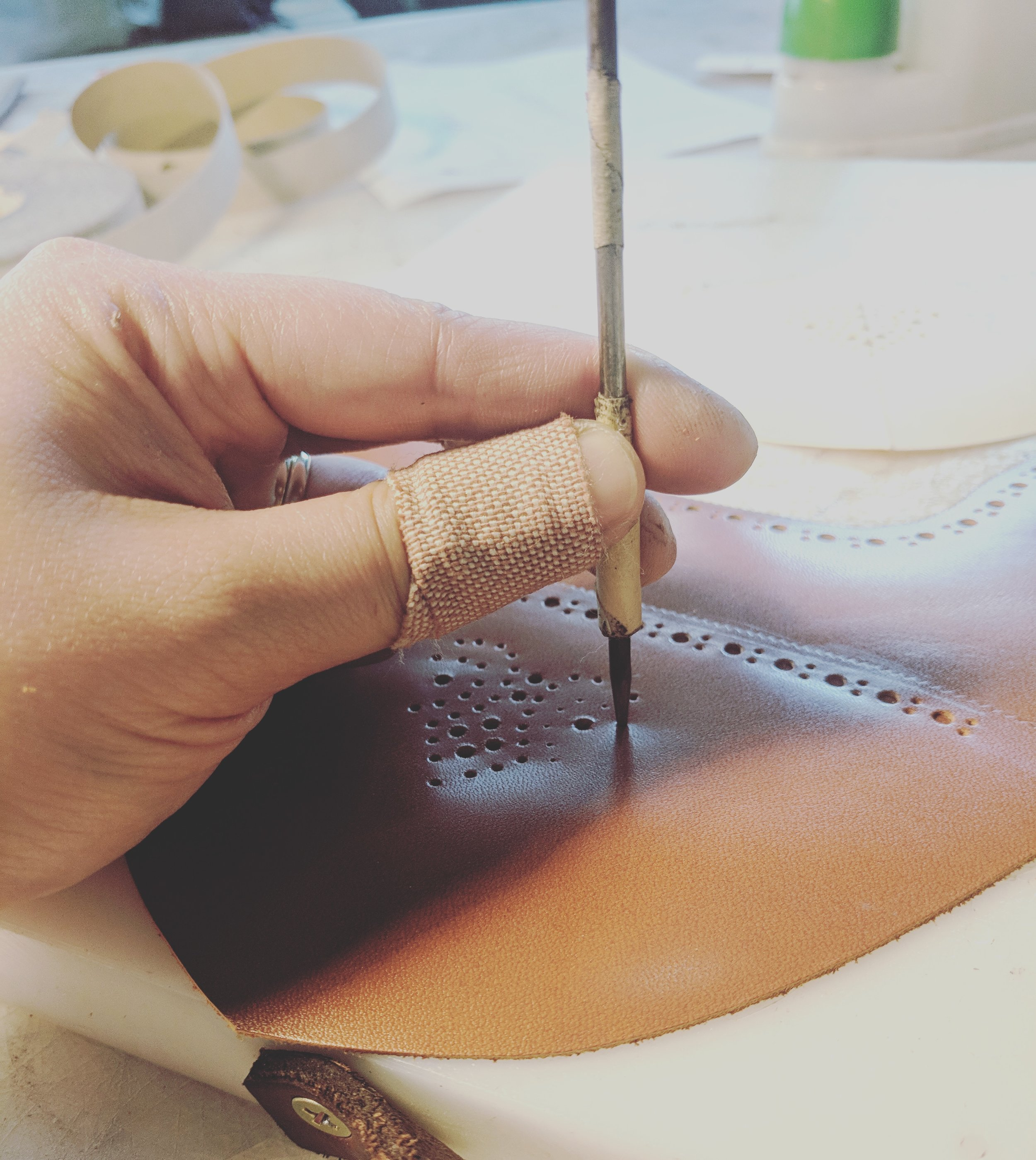 Punching holes to make a medallian in a pair of brogues.