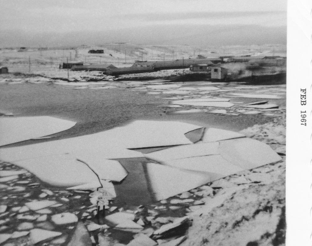 Flóð og klakaburður í lóninu 1967.  Við lónið stendur hitaveitukofi. Að baki honum sést gamla húsið á Sólveigarstöðum.
