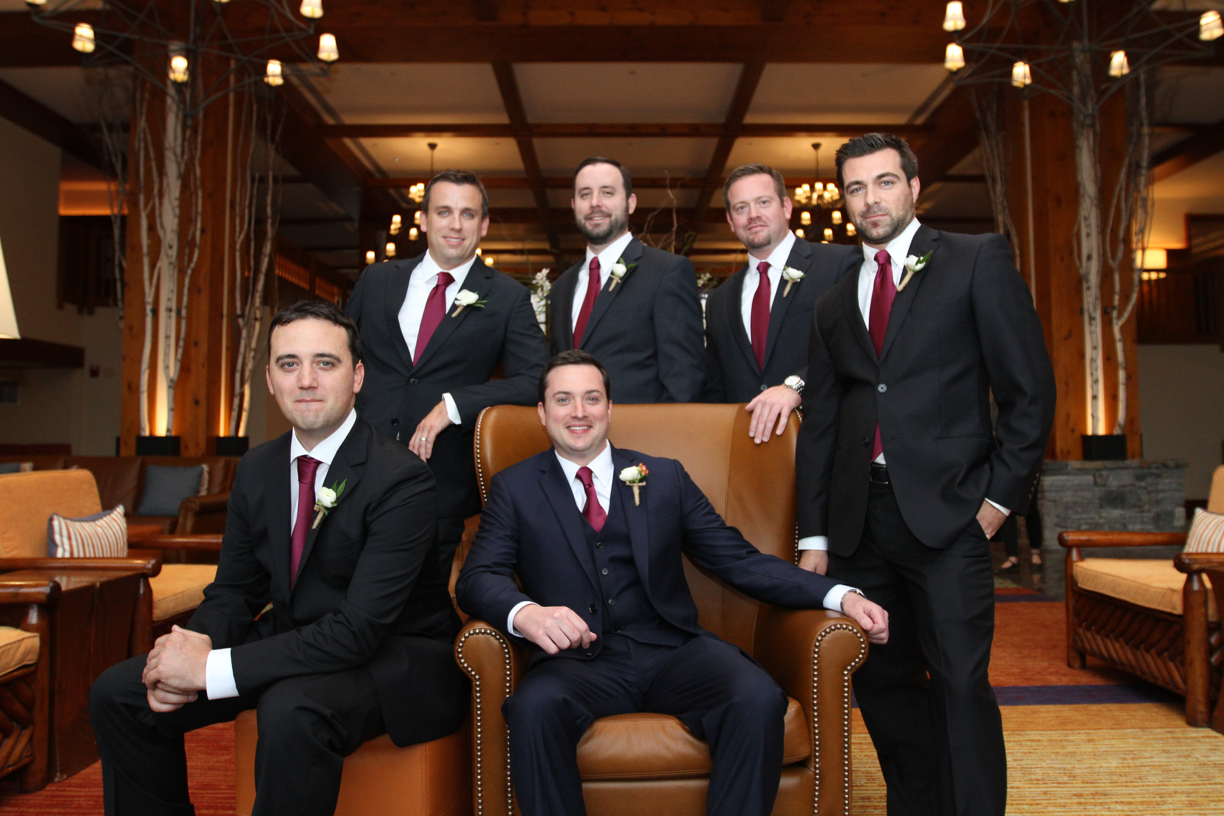 Groom sitting in a brown Leather high backed chair and 5 Groomsmen in Blue Tuxedo in the lobby of Stowe Mountain Lodge.